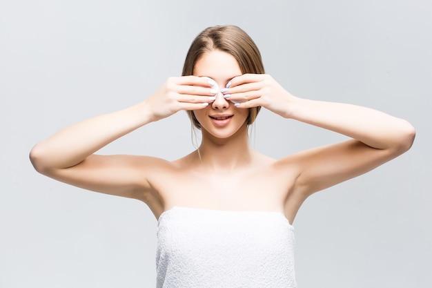 자연 화장을 한 모델은 눈에 두 개의 흰색 스폰지로 얼굴을 닦습니다.
