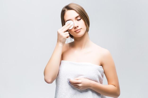자연 화장을 한 모델은 눈에 하얀 스펀지로 얼굴을 닦습니다.