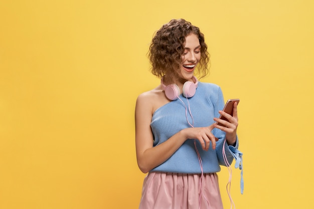 Model with pink headphones holding phone, smiling.