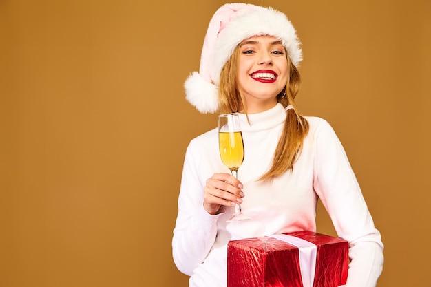 Модель в шляпе санта-клауса и большой подарочной коробке пьет шампанское на золотой стене