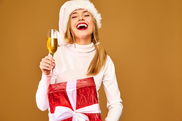 金色の壁にシャンパンを飲むサンタの帽子と大きなギフトボックスのモデル