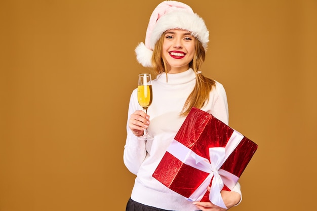 Model with santa hat and big gift box drinking champagne on golden wall