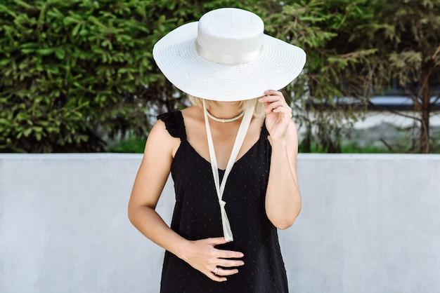 모자 카탈로그의 새로운 컬렉션에서 포즈를 취하는 아름다운 모자에 검은 드레스에 모델 여자