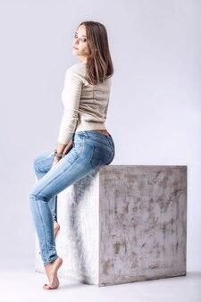 모델, 유행 청바지 여자와 밝은 벽에 인테리어 큐브에 스튜디오에서 전체 길이의 재킷