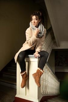 Модель женщина позирует, сидя на перилах ступеней с колоннами
