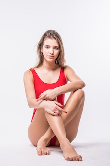 Model woman in red swimming suit is sitting on the floor and holds her legs crossed in front of her body