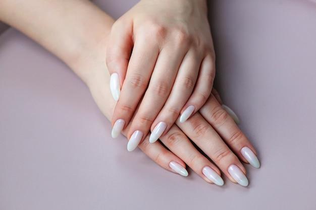 긴 n에 밝은 흰색 누드 셸락 매니큐어를 보여주는 모델 여자
