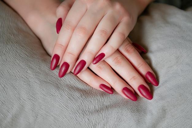 長い爪に赤いシェラックマニキュアを示すモデルの女性