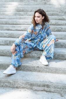 모델 여성이 계단에 앉아 새로운 여름 옷 컬렉션을 입고 포즈를 취하고 있습니다.