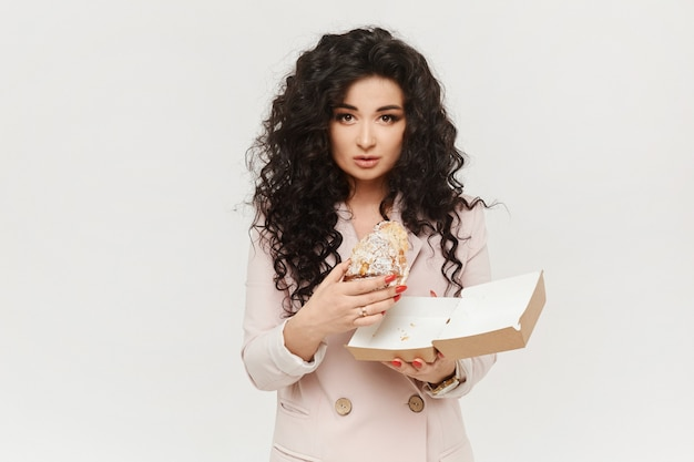 Model woman with black curly hair eating a tasty dessert, isolated