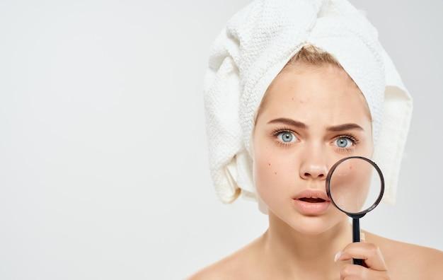 Модель женщины с увеличительным стеклом на светлом фоне и полотенцем на голове