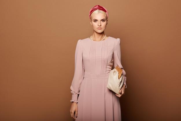 베이지 색 배경 위에 절연 트렌디 한 핑크 드레스에 완벽한 헤어 스타일과 메이크업 모델 여자