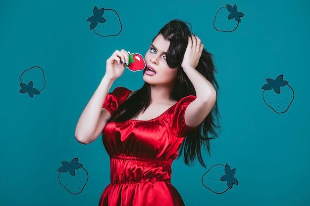 塗られた赤いイチゴと青い背景にポップアートのスタイルで若くて美しいモデルの女性