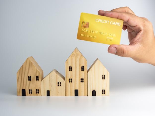 モデルの木造住宅とクレジットカードを持っている人の手。住宅事業のコンセプト。