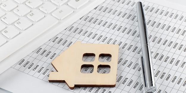 木造住宅とキーボードをモデル化します。チャートの背景に不動産投資コンセプトの画像