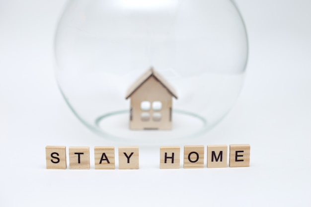 Model of a wooden house under a glass dome and wooden letters with the inscription stay home