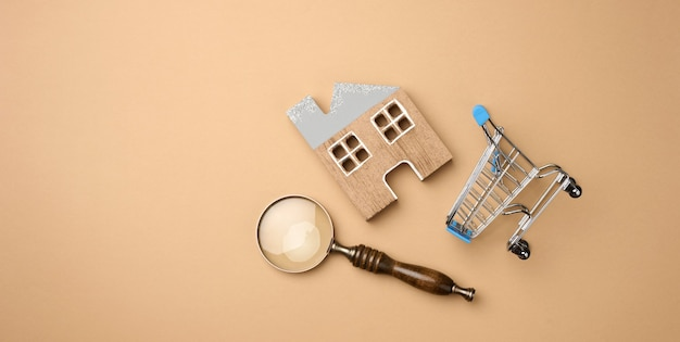 Model of a wooden house, a miniature shopping cart and a magnifying glass on a light brown background. home search concept for rent, purchase, mortgage