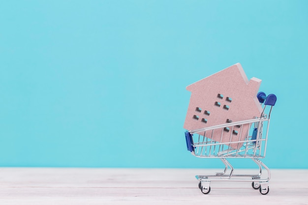 Model of the wooden house in shopping cart on wooden table