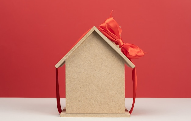 Model of a wooden house tied with a red silk ribbon, concept of real estate purchase, mortgage