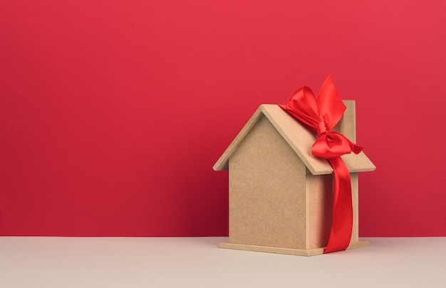 Model of a wooden house tied with a red silk ribbon on a red background, concept of real estate purchase, mortgage. copy space
