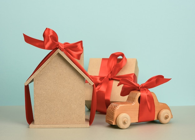 Model of a wooden house tied with a red silk ribbon and a wooden car on a blue background, the concept of purchase, mortgage