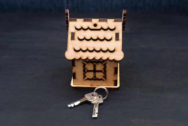 Model of a wooden house with keys. building, borrowing, real estate or buying a new home.