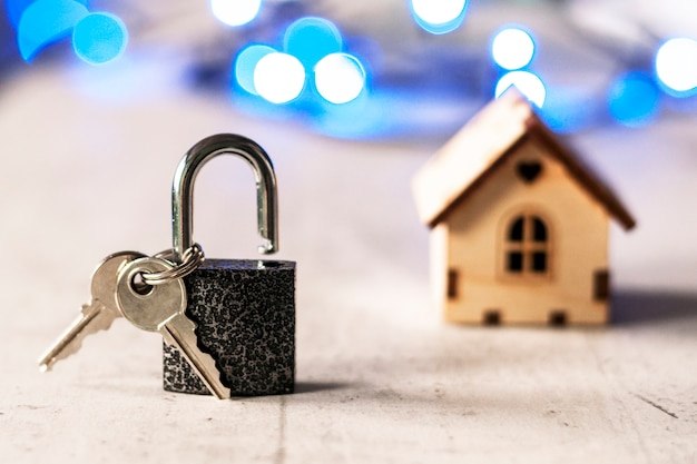Model of a wooden house with a lock and keys and bokeh