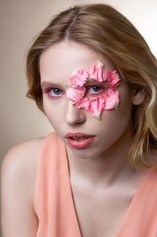 モデルが機能しています。顔に花びらのあるポーズを見せながら、ピンクのアイシェードが効く魅力的なプロモデル