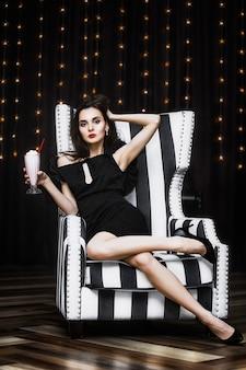 Модель молодой женщины красивая и роскошная сидит в черно-белом полосатом кресле модно и стильно