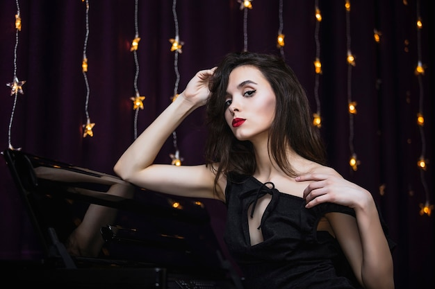 Model young woman beautiful and luxurious on the background of the piano and lights fashionable and stylish
