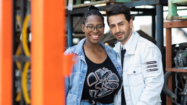 Моделирование портретного фото. афро-американская работница и менеджер латиноамериканского мужчины, работающие вместе в старом магазине склада авто и запчастей.