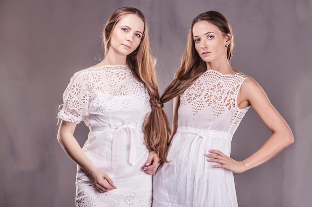 긴 머리를 가진 부드러운 드레스를 입은 아름다운 여성 여자 친구가 서로 다정하게 의사 소통합니다.