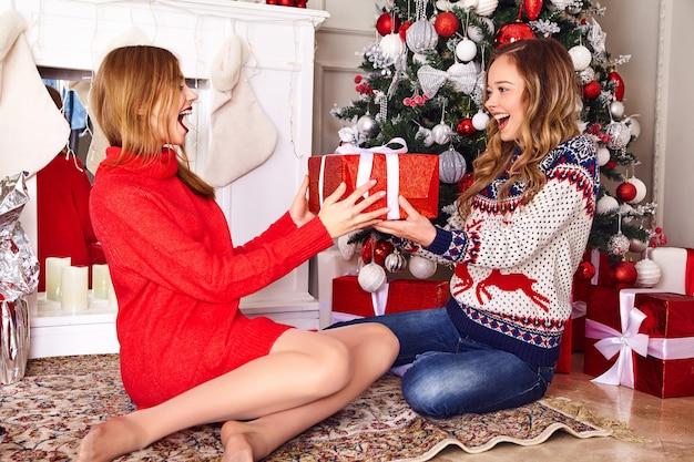 Модели в теплых зимних свитерах сидят возле украшенной елки в канун нового года.