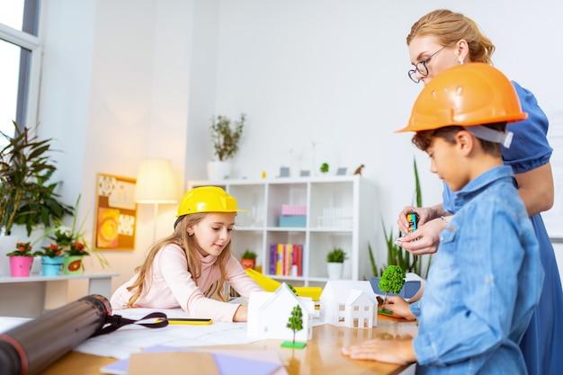 木のモデル。家のモデリングを勉強しながら、木のモデルを置き、テーブルの上に構築する男の子と女の子