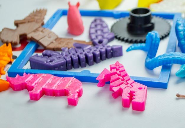 Модели напечатаны на 3д принтере. яркие красочные объекты, напечатанные на 3d-принтере на столе крупным планом. моделирование наплавленного осаждения, fdm. концепция современной прогрессивной аддитивной технологии для 3d-печати.