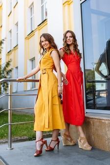 계단에 서있는 동안 밝은 노란색과 빨간색 드레스를 과시하는 모델