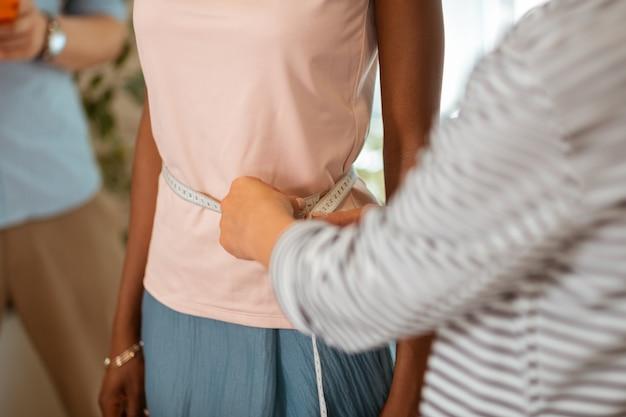モデルウエスト。巻尺でモデルのウエストを測定する女性の仕立て屋