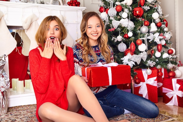 Models in warm winter sweaters sitting near decorated christmas tree at new year eve.