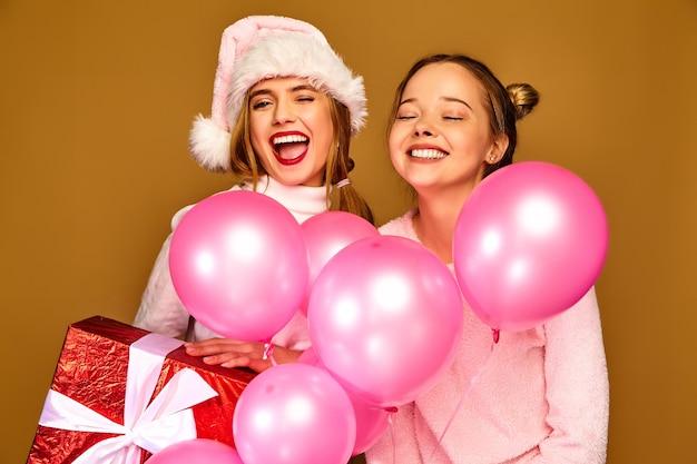 クリスマスに大きなギフトボックスとピンクの風船を持つモデル