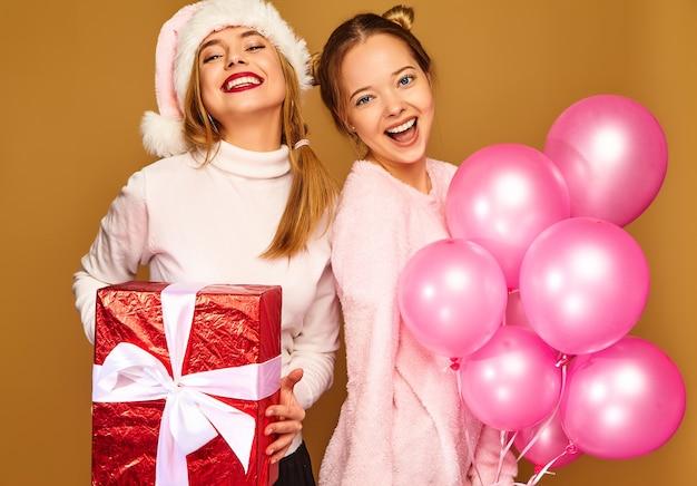 Модели с большой подарочной коробкой и розовыми воздушными шарами на рождество