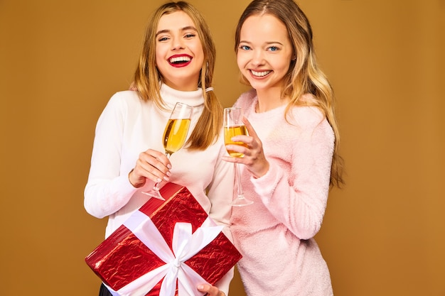 Models with big gift box drinking champagne in glasses celebrating new year