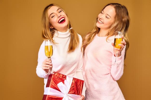 Modelli con grande confezione regalo bevendo champagne in bicchieri per celebrare il nuovo anno