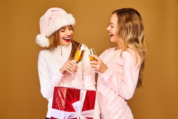Модели с большой подарочной коробкой пьют шампанское в бокалах, празднуют новый год
