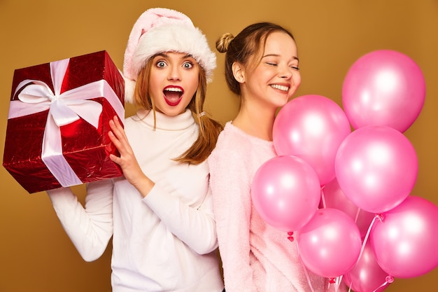 Models with big gift box and pink balloons on christmas