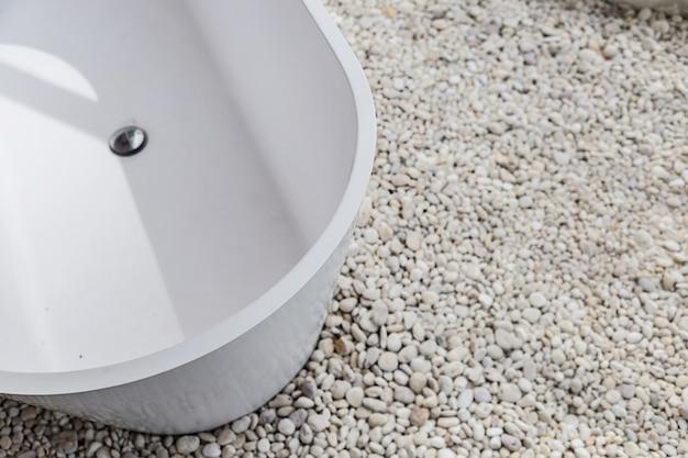 白い小石の汚れの床と白いmoden浴槽