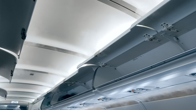Moder airplane ceiling and open luggage compartment.