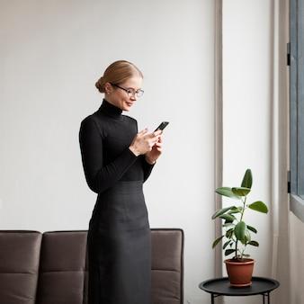Модерная женщина, стоящая и использующая мобильный телефон