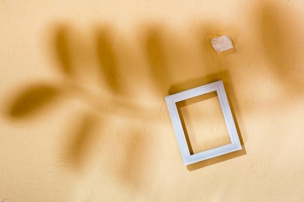 現代の抽象的なライフスタイルの背景:コンクリート、空のフォトフレームと葉からの柔らかい影の石。上面図。テキストの場所
