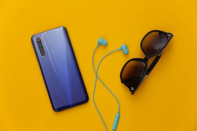 현대적인 액세서리. 파란색 이어폰, 노란색 선글라스와 현대 스마트 폰