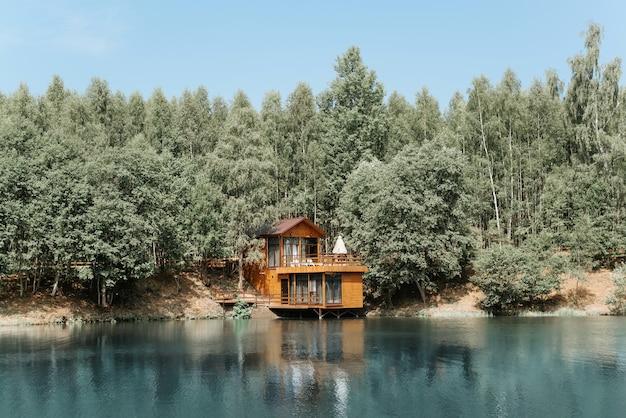 호수에 현대적인 미적 목조 주택입니다. 시골집의 외관, 여름날 숲 근처 물 위에 있는 별장.